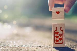 Mano sosteniendo un cubo de madera con icono de signo de corazón con luz solar natural foto
