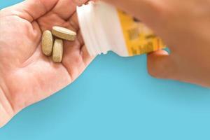 Vista superior de la tableta de medicina orgánica alternativa en la mano de la mujer foto
