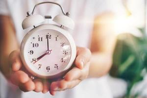 Selective focus of alarm clock with nature bokeh background