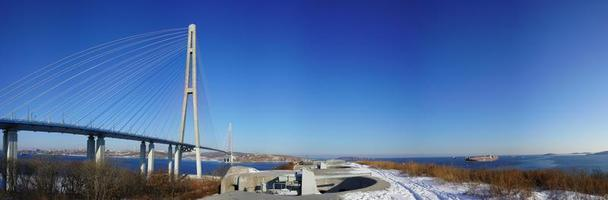 Panorama of Voroshilovskaya Battery and Russky Bridge against a clear blue sky in Vladivostok, Russia photo