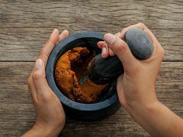 Grinding red curry paste photo
