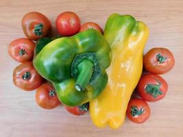 Bell peppers and tomatoes on a beige table background photo