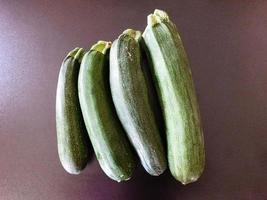 Four zucchinis on a dark table background