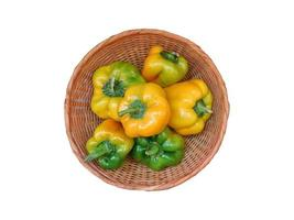 Green and yellow peppers in a wicker basket on a white background photo