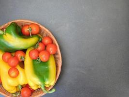 Bell peppers and tomatoes in a wicker basket on a dark table background photo