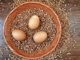 Brown eggs and cereal grains in a wicker basket on a wooden table background photo