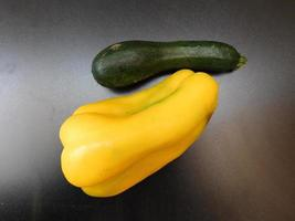 Green and yellow peppers on a wooden table background photo