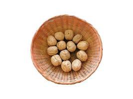 Whole walnuts in a wicker basket on white background