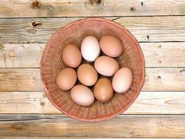 Brown eggs in a wicker basket on a wooden table background