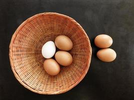 Huevos marrones en una canasta de mimbre sobre un fondo de mesa oscuro