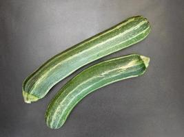 Two zucchinis on a dark table background