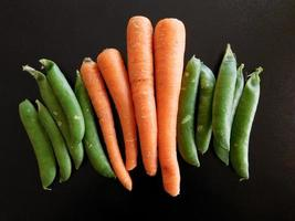 Snap peas and carrots on a black background