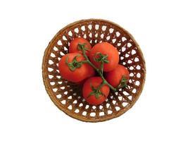 Tomates en una cesta de mimbre sobre un fondo blanco. foto
