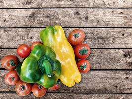Bell peppers and tomatoes on a wood table background
