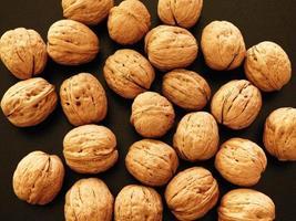 Pile of whole walnuts on black background