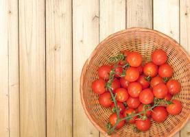 Tomates en una canasta de mimbre sobre un fondo de mesa de madera foto
