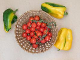 Tomatoes in a wicker basket next to bell peppers on a beige table background photo