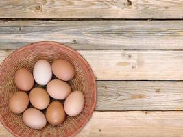 Brown eggs in a wicker basket on wooden table background