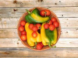 Bell peppers and tomatoes in a wicker basket on a wood table background photo