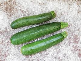 Three zucchinis on a bed of plastic straw background