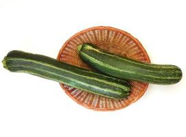Two zucchinis in a wicker basket on a white background