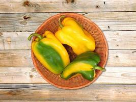 Green and yellow peppers in a wicker basket on a wooden table background photo