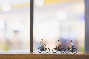 Viajeros en miniatura con bicicletas en un puente de madera foto