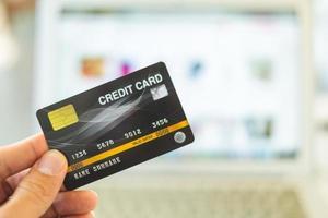 Manos sosteniendo una tarjeta de crédito y usando una computadora portátil, concepto de compras en línea foto