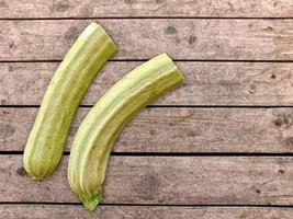 Two zucchinis on a wood table background