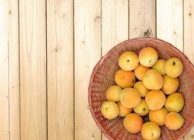 Apricots in a wicker basket on wooden table background photo