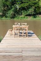 escritorio y silla en un largo puente de madera cerca del río