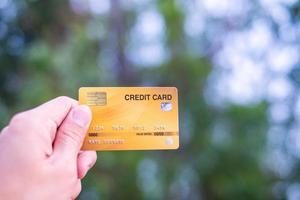 una mano que sostiene una tarjeta de crédito con fondo bokeh, concepto de libertad financiera foto