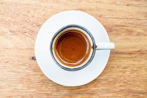 Una taza de café espresso caliente sobre un fondo de madera