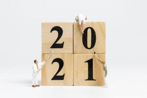 Miniature workers painting the number 2021, Happy New Year concept