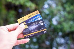 A hand holding credit cards with a bokeh background, financial freedom concept photo