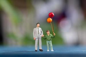 Miniature happy family holding balloons on a blurry background