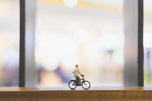 Viajero en miniatura con una bicicleta sobre un puente de madera foto