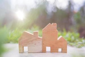 Wooden house model on the ground, housing and real estate concept photo