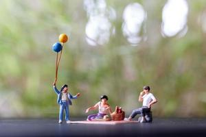Miniature people of a happy family sitting on a mat during a picnic in the park