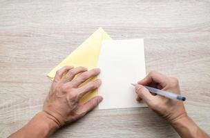 Male hands writing on an empty card on a wooden table photo