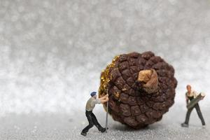 Miniature workers preparing a Christmas pine cone, Christmas and Happy New Year concept