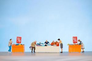 Gente en miniatura comprando artículos con descuento en una mesa