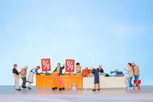 Gente en miniatura comprando artículos con descuento en una mesa foto