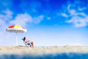 Miniature people sunbathing on the beach, summertime concept photo