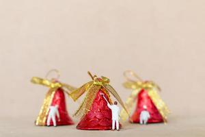 Miniature workers painting a Christmas decoration, Christmas and Happy New Year concept photo