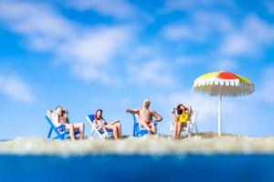 Miniature people sunbathing on the beach with a blue sky background, summertime concept photo