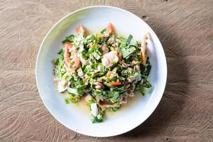 Vista superior de hojas de té verde con ensalada de atún en una mesa de madera