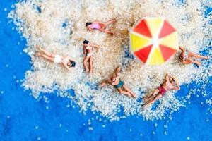 Miniature people sunbathing on the beach, summertime concept
