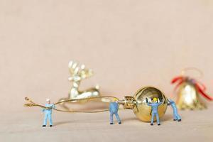 Trabajadores en miniatura trabajando en adornos navideños, navidad y feliz año nuevo concepto foto