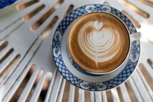 latte art en una taza de café en la mesa plana laical